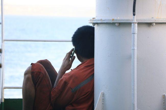 Marin assis à bord, appelant sa famille